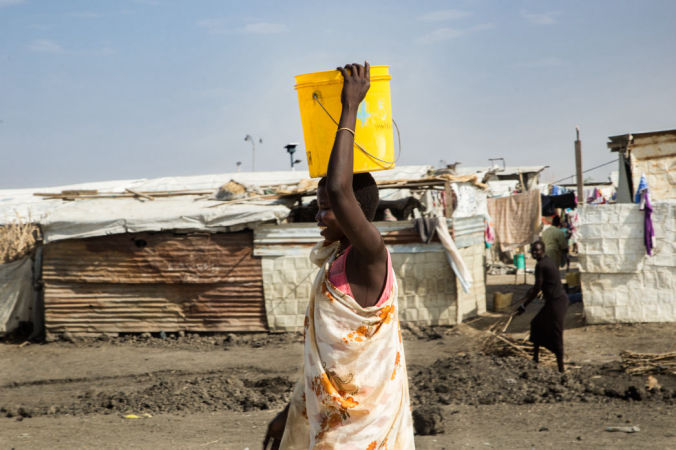 A woman carries a bucket of water in the Malakal Protection of Civilian (PoC) site, in north-east South Sudan. Photo by Igor Barbero/MSF.